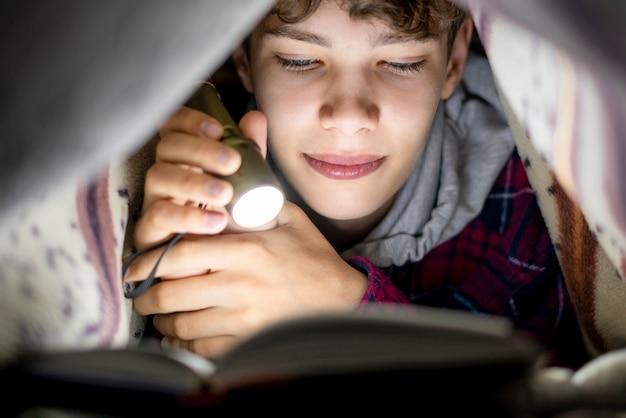 Portret czyta książkę z lekkim lying on the beach pod koc przy nocą f młody nastolatek