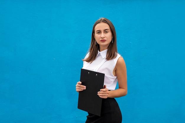 Portret damy biznesu pisze w schowku na białym tle na niebiesko. pojęcie zawodu lub pracy