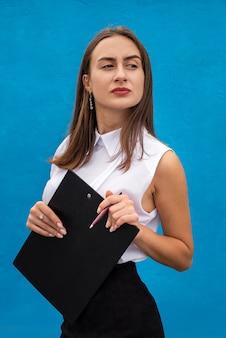 Portret damy biznesu pisze w schowku na niebieskim tle. pojęcie zawodu lub pracy