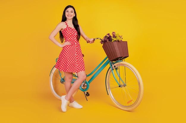 Portret damy z rowerową ręką na biodrach obuwie w kropki w czerwonej mini sukience na żółtym tle