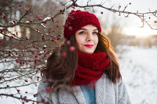 Portret delikatnej dziewczyny w szarym płaszczu, czerwonym kapeluszu i szaliku w pobliżu gałęzi ośnieżonego drzewa.