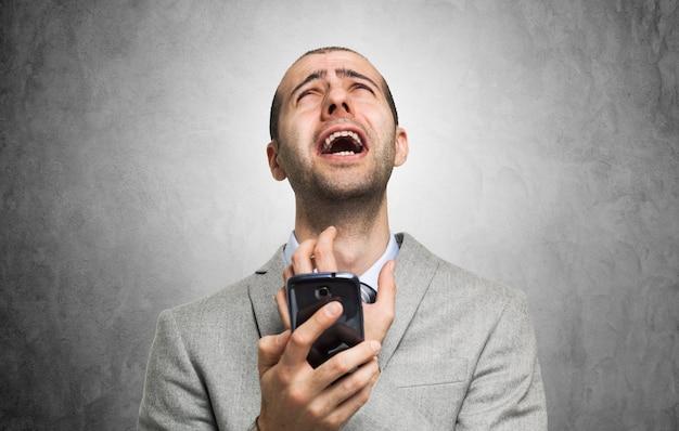 Portret desperacki mężczyzna trzyma jego telefon komórkowego