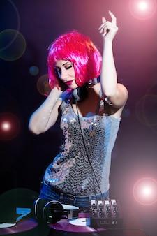 Portret dj słuchawki winylowy dysk plaża gra sprzęt lato dyskoteka dziewczyna party retro vintage różowy czerwony biurko mikser glamour dysk płyty okulary młoda kobieta gospodarstwa