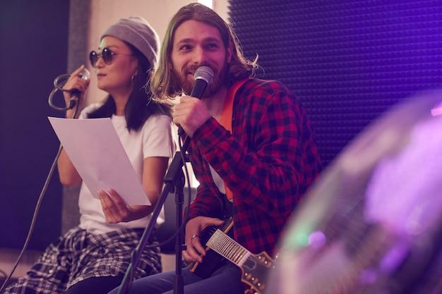Portret długowłosy młody człowiek gra na gitarze i śpiewa do mikrofonu podczas próby