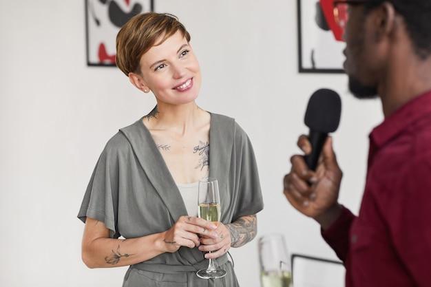 Portret do pasa wytatuowanej eleganckiej kobiety udzielającej wywiadu podczas otwarcia wystawy w galerii sztuki współczesnej,