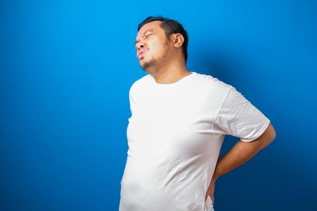 Portret dobrze wyglądającego młodego azjatyckiego mężczyzny w białej koszulce z bólem na plecach