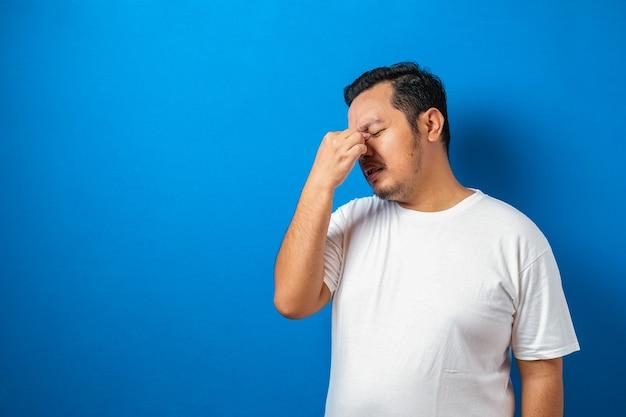 Portret dobrze wyglądającego młodego azjatyckiego mężczyzny w białej koszulce ze stresem lub bólem głowy;