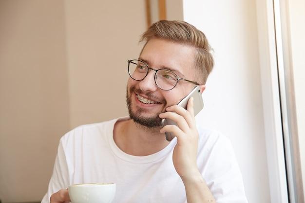 Portret dobrze wyglądającego młodego faceta, szeroko uśmiechającego się, trzymającego filiżankę kawy w jednej ręce i telefon w drugiej, będąc w dobrym nastroju, w okularach i białej koszulce