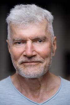 Portret dobrze wyglądającego siwego starszego mężczyzny w białej koszulce koncepcja sportu i zdrowia