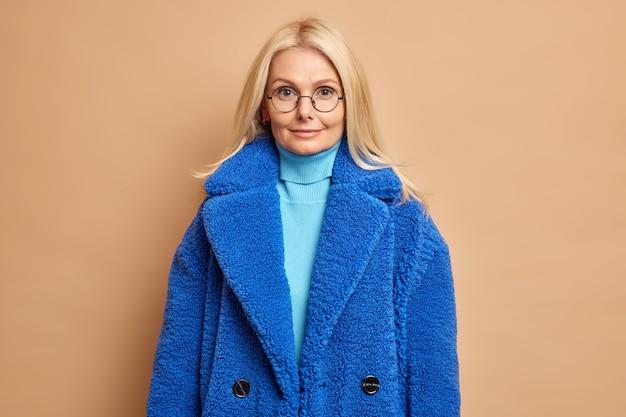 Portret dobrze wyglądającej kobiety w średnim wieku wygląda spokojnie dresed w okrągłych okularach niebieski płaszcz zimowy z golfem.