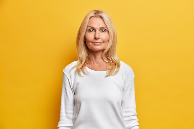 Portret dobrze wyglądającej kobiety w średnim wieku z pomarszczoną twarzą naturalna uroda blond włosy patrzy prosto w kamerę ma spokojny wyraz twarzy ubrany w biały swobodny sweter