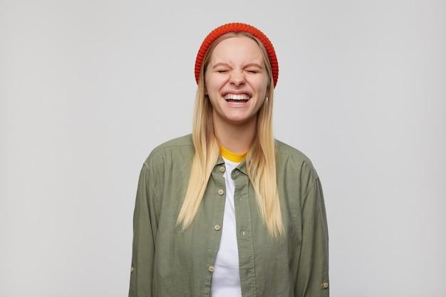 Portret dobrze wyglądającej młodej kobiety blondynka w czerwonym kapeluszu, trzymając oczy zamknięte, śmiejąc się radośnie, trzymając ręce w dół podczas pozowania na niebiesko