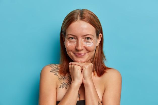 Portret dobrze wyglądającej piegowatej rudowłosej kobiety trzyma dłonie pod brodą, nakłada przezroczyste plastry kolagenowe pod oczy, nawilża skórę i usuwa zmarszczki, pozuje z odkrytymi ramionami