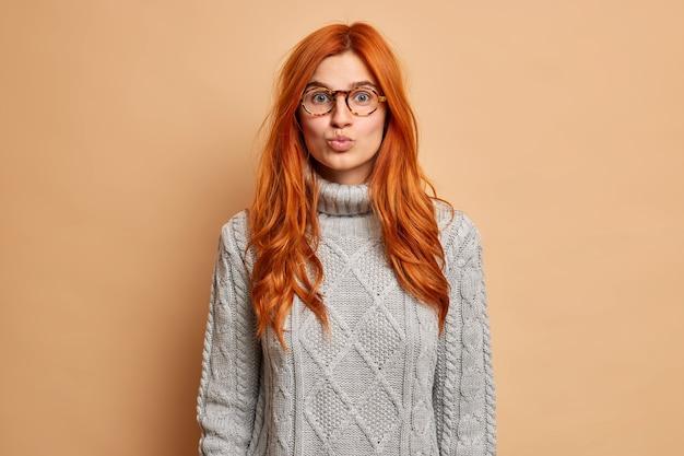 Portret dobrze wyglądającej rudowłosej kobiety utrzymuje usta zaokrąglone ma romantyczny wyraz twarzy chce pocałować kogoś, kto nosi szary sweter.