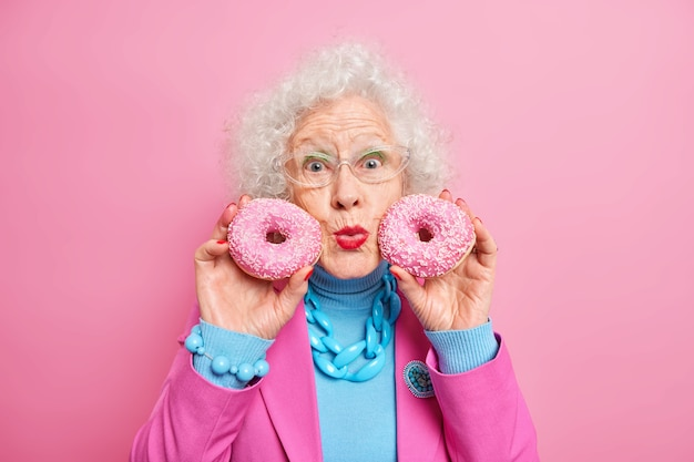 Portret dobrze wyglądającej siwej kobiety trzyma pączki w pobliżu twarzy zaokrąglone usta cieszy się życiem ma słodycze nosi okulary modne ubrania