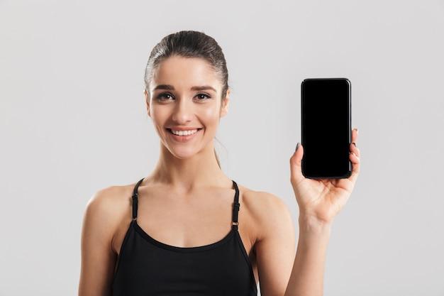 Portret dobrze zbudowana uśmiechnięta kobieta pokazuje czarnego ekran telefonu, odizolowywający nad szarości ścianą
