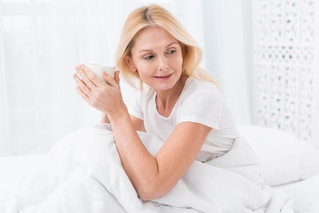 Portret dojrzała kobieta w łóżku patrzeje daleko od