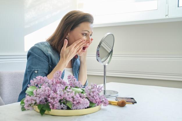 Portret dojrzała kobieta z makijażu lustrem