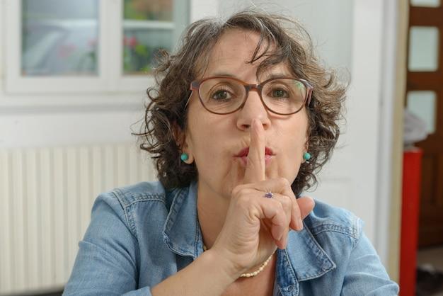 Portret dojrzała kobieta z palcem na wargach