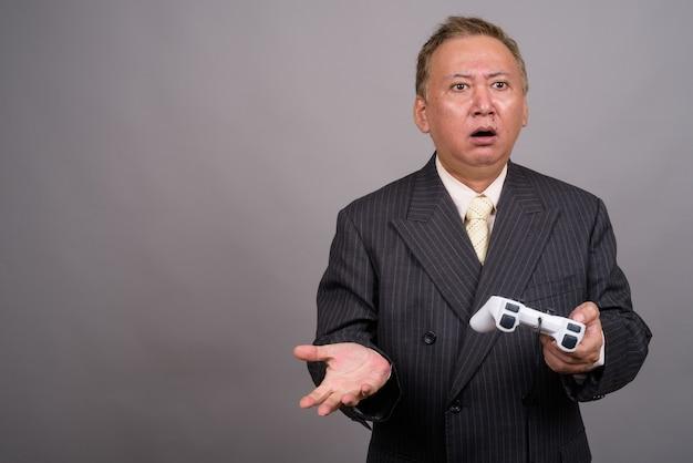 Portret dojrzałego biznesmena azjatyckich przeciw szarej ścianie