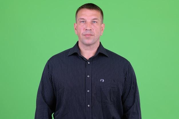 Portret dojrzałego biznesmena macho przeciwko klucz chrominancji z zieloną ścianą