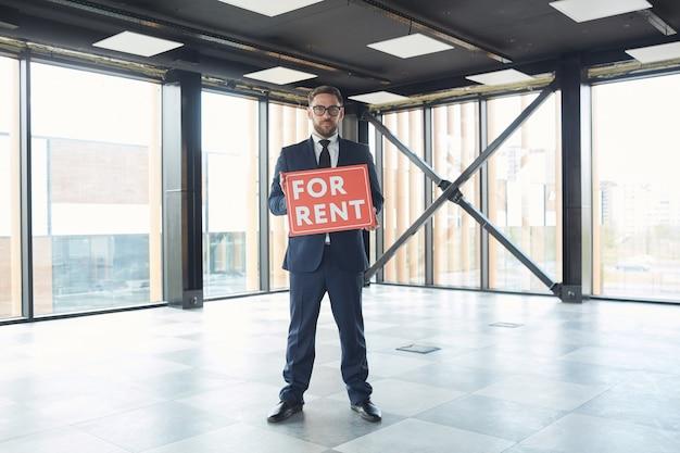 Portret dojrzałego biznesmena w wizytowym i trzymając tabliczkę, sugerując biura do wynajęcia