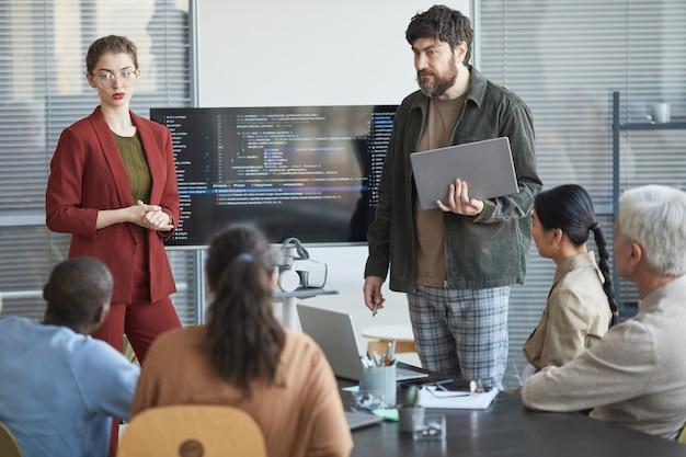 Portret dojrzałego brodatego mężczyzny przedstawiającego prezentację w biurze dla zróżnicowanego zespołu it stojącego za kodem na ekranie