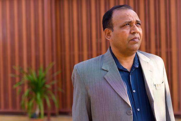 Portret dojrzałego indyjskiego biznesmena z nadwagą z cofającą się linią włosów na sobie garnitur na ulicy