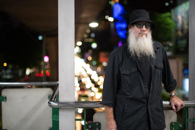 Portret dojrzałego mężczyzny brodaty turysta zwiedzanie ulic miasta bangkoku w tajlandii w nocy