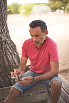 Portret dojrzałego mężczyzny korzystającego ze smartfona na zewnątrz