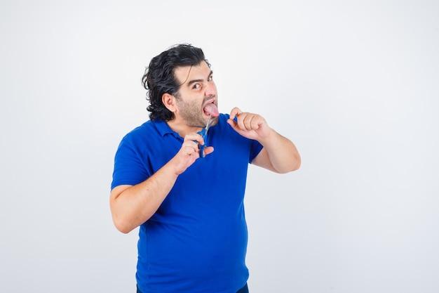 Portret dojrzałego mężczyzny próbującego przeciąć język nożyczkami w niebieskiej koszulce i patrząc agresywnie z przodu