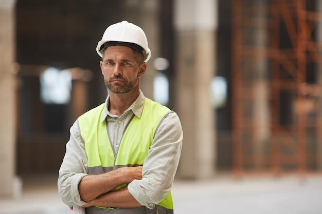 Portret dojrzałego pracownika budowlanego w pasie stojąc z rękami skrzyżowanymi na budowie,