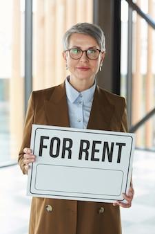 Portret dojrzałej bizneswoman w okularach trzymając tabliczkę do wynajęcia w dłoniach stojąc w biurze