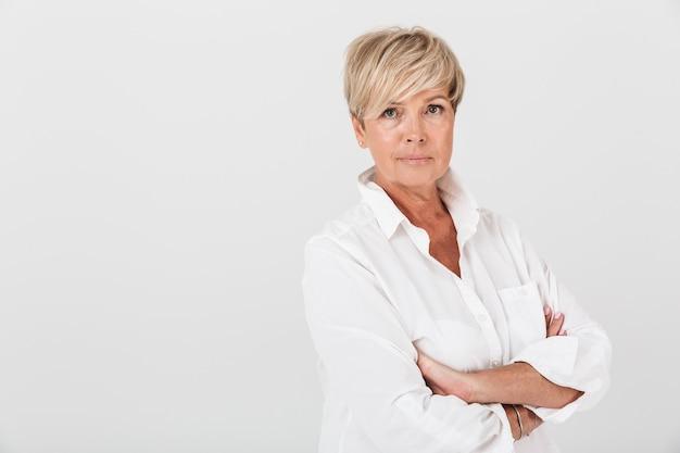 Portret dojrzałej kobiety pozuje do kamery ze spokojnym spojrzeniem i skrzyżowanymi rękami na białym tle nad białą ścianą w studio