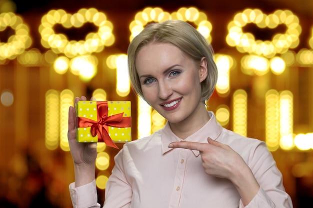 Portret dojrzałej kobiety prezentującej żółte pudełko upominkowe