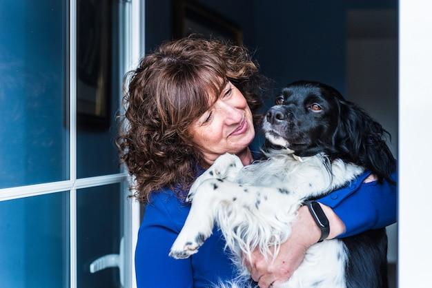 Portret dojrzałej kobiety trzymającej psa w ramionach
