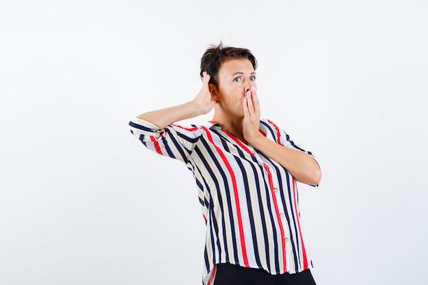 Portret dojrzałej kobiety trzymającej rękę na ustach podczas podsłuchiwania prywatnej rozmowy w pasiastej koszuli i wyglądającej na zaskoczonego widoku z przodu