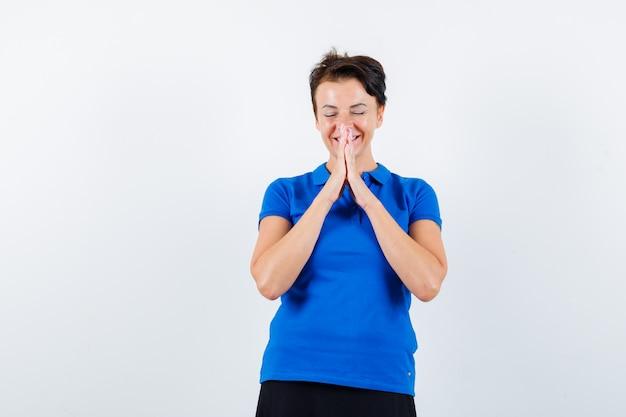 Portret dojrzałej kobiety trzymającej się za ręce w geście modlitwy w niebieskiej koszulce i patrząc wdzięczny widok z przodu