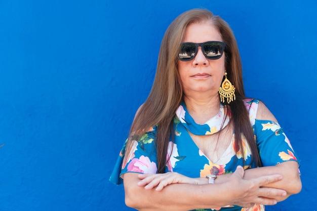 Portret dojrzałej kobiety w okularach przeciwsłonecznych.