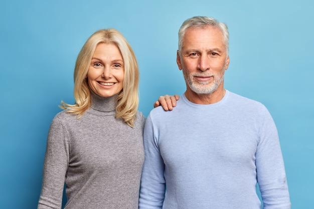 Portret dojrzałej pary stoi obok siebie, patrzy prosto w kamerę, ma zadowolone miny