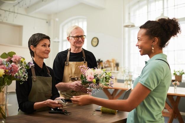 Portret dojrzałej pary wręcza bukiet uśmiechniętej klientce podczas pracy w kwiaciarni...