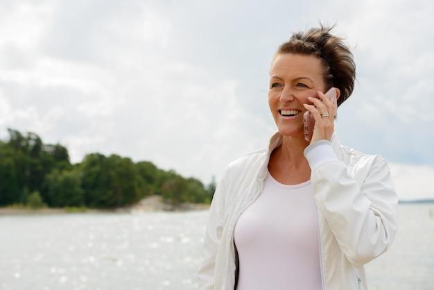 Portret dojrzałej pięknej kobiety przed malowniczym widokiem na jezioro i niebo w przyrodzie