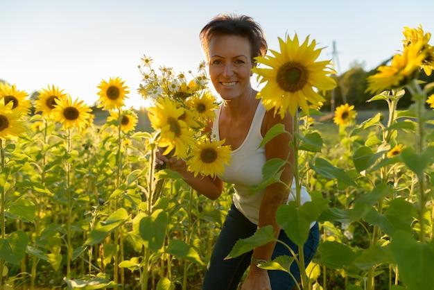 Portret dojrzałej pięknej skandynawskiej kobiety w dziedzinie kwitnących słoneczników na zewnątrz
