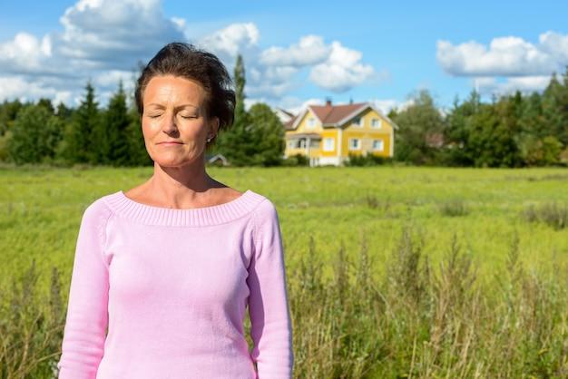 Portret dojrzałej pięknej skandynawskiej kobiety z krótkimi włosami relaksujący w naturze na świeżym powietrzu