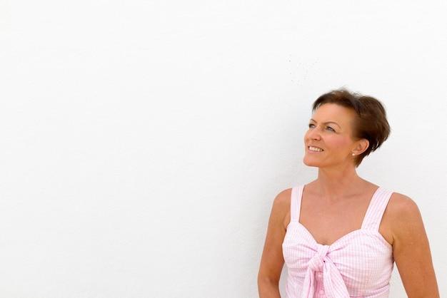 Portret dojrzałej pięknej skandynawskiej turystki z krótkimi włosami na białej ścianie jako ściana na zewnątrz
