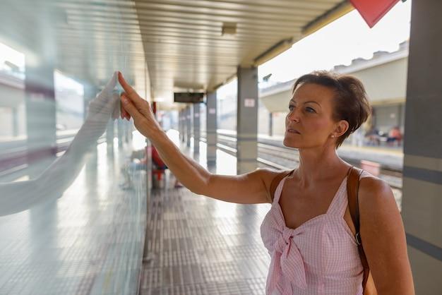 Portret dojrzałej pięknej skandynawskiej turystki z krótkimi włosami na dworcu