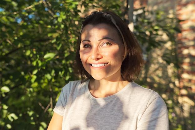 Portret dojrzałej uśmiechniętej kobiety w ogrodzie w pobliżu domu, zachód słońca na twarzy kobiety, kopia przestrzeń