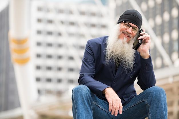 Portret dojrzały biznesmen łysy z długą brodą w okularach na ulicach miasta na zewnątrz