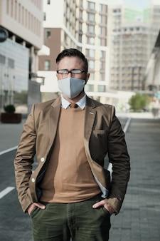 Portret dojrzały biznesmen w masce ochronnej patrząc na kamery podczas spaceru ulicą w mieście
