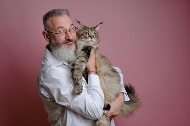 Portret dojrzały, brodaty mężczyzna trzymający swojego kota maine coon, różowe ściany